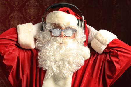Santa Claus is listening to music in headphones. Christmas. photo