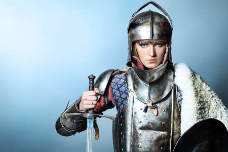 traditional weapon: Portrait of a medieval female knight in armour over grey background.