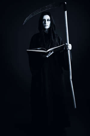 satanic: Woman death reaper over black background. Halloween.