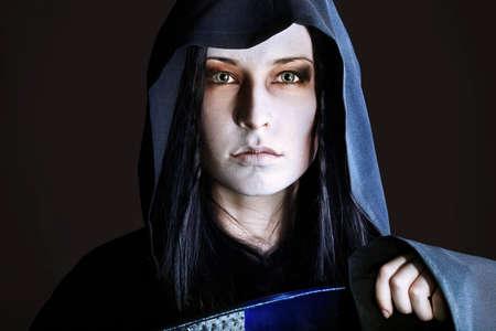 satanic: Woman death reaper over black background. Halloween.