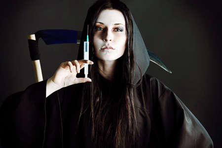 Woman death reaper with syringe over black background. Stock Photo - 8284706