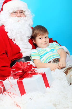 Christmas theme: Santa Claus and little boy with presents. Stock Photo - 8284668