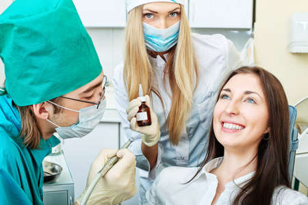 Shot of a young woman with dentists in a dental surgery. Healthcare, medicine. Stock Photo - 8303930