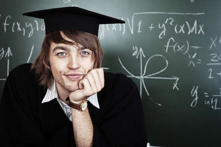 Educational theme: graduating student in academic gown in a classroom. Stock Photo - 8312937