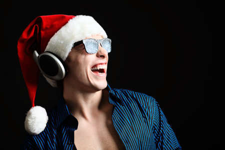 Portrait of a funny young man in Santa Claus hat and headphones. Christmas. photo