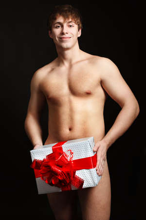 Portrait of a handsome muscular young man  holding a present. Christmas. photo