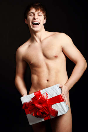 Portrait of a handsome muscular young man  holding a present. Christmas. Stock Photo - 8312927