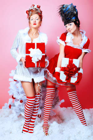Two beautiful young women in Christmas clothes posing with New Year tree. Stock Photo - 8312945