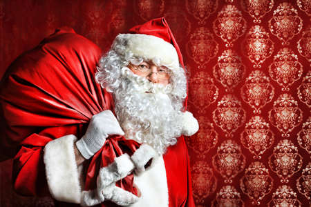 Portrait of Santa Claus with a bag of presents. Christmas.