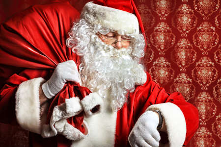 father christmas: Portrait of Santa Claus with a bag of presents and looking at his watch. Christmas.