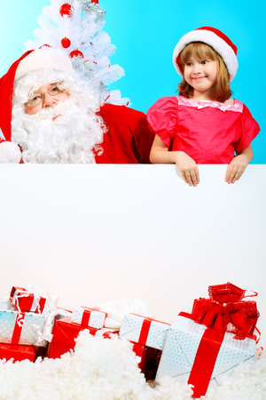 Christmas theme: Santa Claus and little girl holding white board.  photo