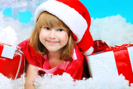Christmas theme: little girl in santa hat lying on snow with presents.  photo