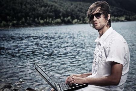 Handsome young man sitting near the sea with a laptop. photo