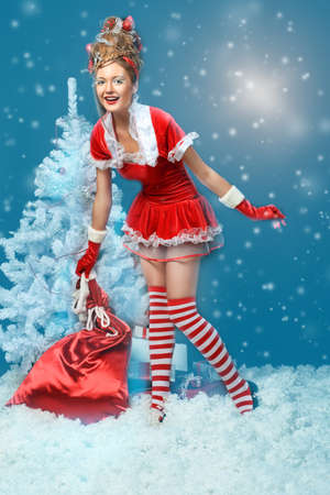 Fashionable young woman in Santa Claus clothes with presents over black background. Stock Photo - 8318846