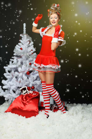 Fashionable young woman in Santa Claus clothes with presents over black background. photo