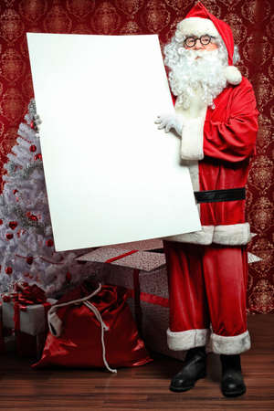 Portrait of Santa Claus holding white board. Christmas. photo