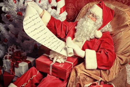 santa: Santa Claus with presents and New Year tree at home. Christmas.