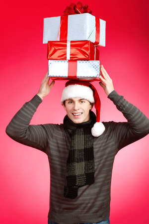 Portrait of a handsome young man in Santa Claus hat holding presents. Christmas. photo