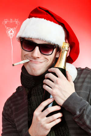 Portrait of a handsome young man in Santa Claus hat celebrating Christmas. photo