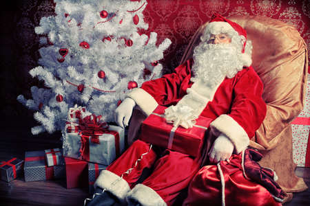 Santa Claus with presents and New Year tree at home. Christmas. Stock Photo - 8318871
