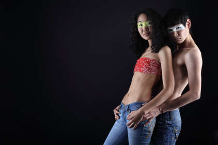 Shot of a couple of young people with painted eyes posing together over black background.  photo