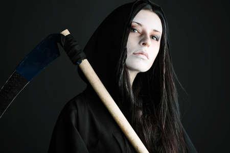 scythe: Woman death reaper over black background. Halloween.