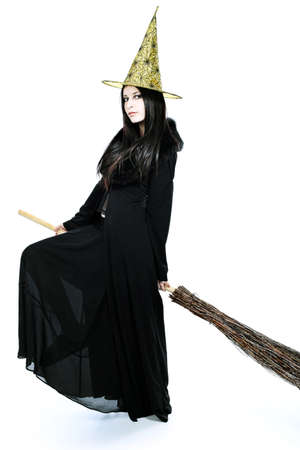 Halloween witch with a broom isolated over white background. photo