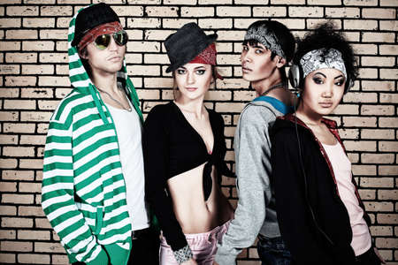 Group of trendy teenagers posing together against a brick wall.  photo