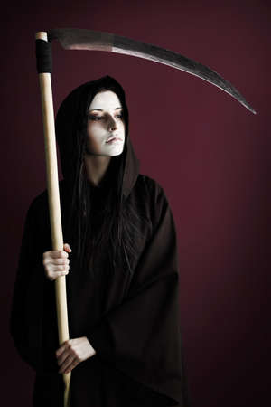 Woman death reaper over black background. Halloween. photo