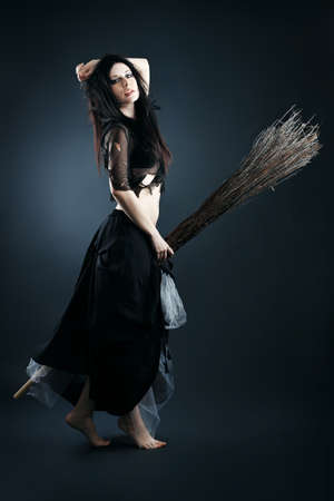Halloween witch with a broom over black  background. photo