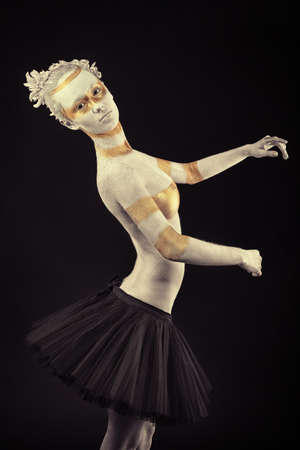 bodypainting: Artistic woman painted with  white and bronze colors, over black background. Body painting project.