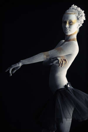 Artistic woman painted with  white and bronze colors, over black background. Body painting project. Stock Photo - 8318903