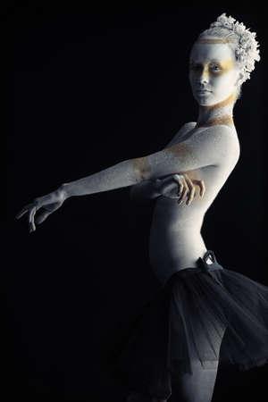 body paint: Mujer art�stica pintado con los colores blanco y bronce, sobre fondo negro. Proyecto de pintura de cuerpo.  Foto de archivo