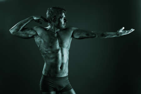 black moor: Portrait of a muscular man painted with black color. Body painting project.