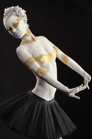 Artistic woman painted with  white and bronze colors, over black background. Body painting project.  photo