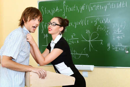 angry teacher: Educational theme: angry teacher with her student at a classroom. Stock Photo