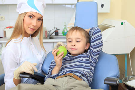 Shot of a smiling little boy with dentist in a dental surgery. Healthcare, medicine. photo