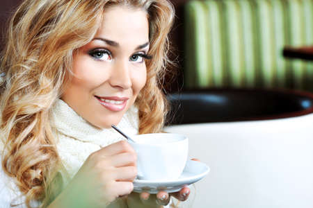 caf: Beautiful young woman with a cup of tea at a caf