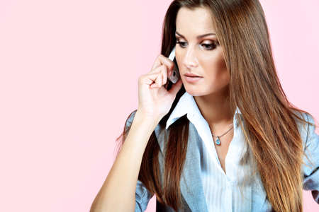 Beautiful woman calling by phone, over pink background. photo