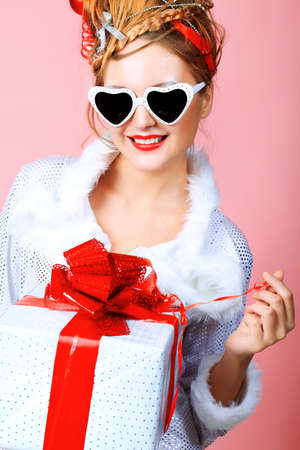 Beautiful young woman in Christmas clothes over pink background. Stock Photo - 8389726