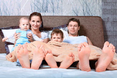 Happy family in bed under cover. photo