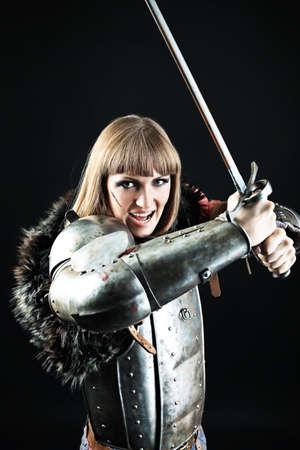 espadas medievales: Retrato de un caballero medieval femenino en armadura sobre fondo negro. Foto de archivo