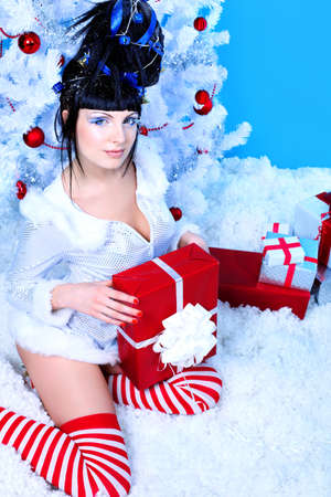 Beautiful young woman in Santa Claus clothes holding a present over Christmas background. photo