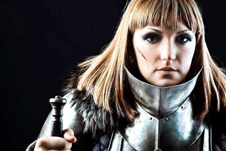 cavaliere medievale: Ritratto di un cavaliere femmina medievale in armatura su sfondo nero.