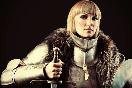 dark blond: Portrait of a medieval female knight in armour over black background.