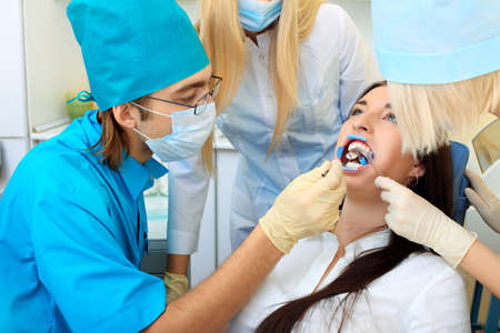 Shot of a young woman with dentists in a dental surgery. Healthcare, medicine. Stock Photo - 8432335