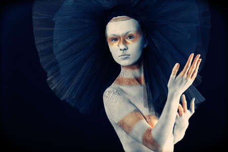 Artistic woman painted with  white and bronze colors, over black background. Body painting project.  Stock Photo - 8445077