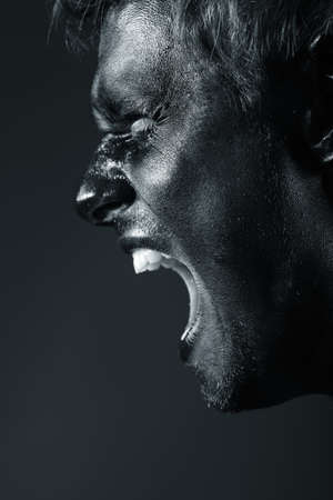 black moor: Portrait of expressive man painted with black color. Body painting project.