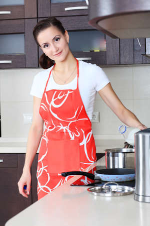 aprons: Woman is cooking on a kitchen at home.