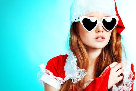 Beautiful young woman in Santa Claus clothes over blue background. photo